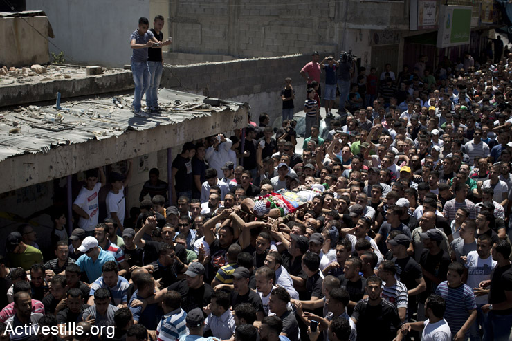 Mourners carry the body of Mohammed al-Araj, 17, in his funeral ceremony at the Qalandiya refugee camp near the West Bank city of Ramallah, on July 25, 2014. Al-Araj was shot and killed the previous night during clashes with the Israeli army. Israeli security forces shot him dead and wounded over 200 other protesters during the massive protest in the West Bank against the Israeli attack on the Gaza strip. (Oren Ziv/Activestills.org)