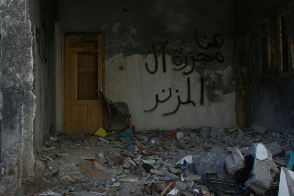 """The room where 17-year-old Abdullah Muzannar and his grandmother were killed by an Israeli airstrike on an adjacent home on November 18, 2012. In the foreground is the grandmother's wheelchair. Spray painted on the wall are the words, """"Here, the Muzannar family massacre."""" (Photo by Lara Aburamadan)"""
