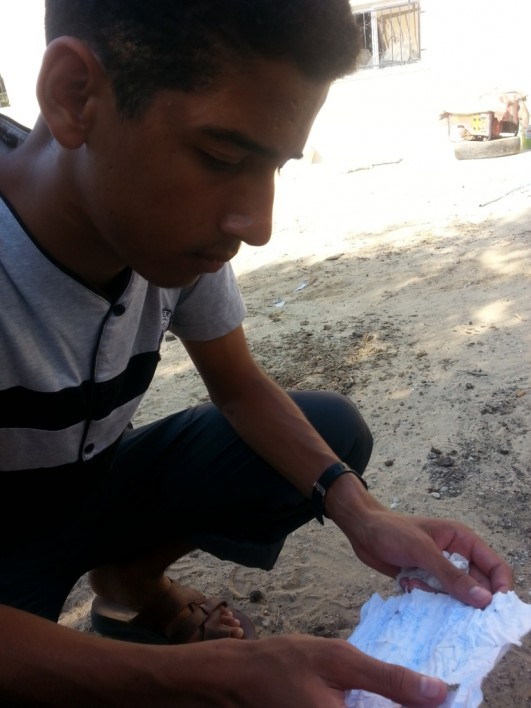 Ahmad Abu Raida holds a the letter he wrote while detained by Israeli soldiers and used as a human shield in Gaza for five days from July 23, 2014 in Khuza'a, Gaza Strip. (photo: DCI-Palestine)