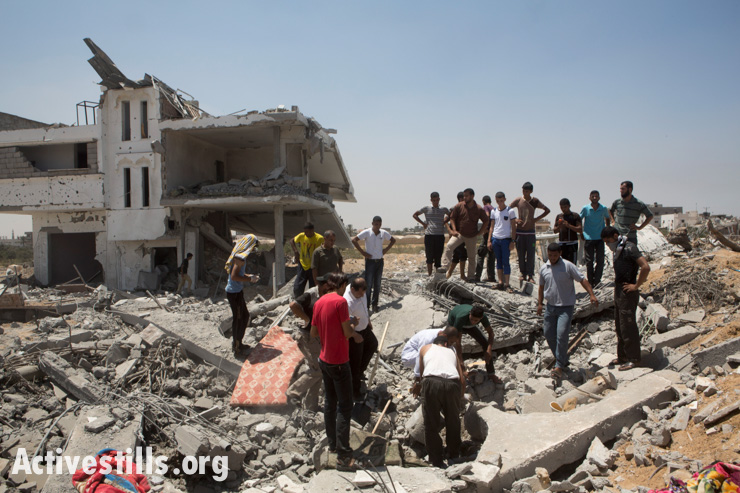 Palestinians gather as some people dig to recover bodies in the village of Khuza'a, east of Khan Younis, Gaza Strip, August 1, 2014.