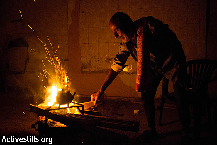 Abu Alaa makes a fire to prepare tea for the family. There has been no gas in the house after the shelling of Beit Hanoun. August 11, 2014. (Basel Yazouri/Activestills.org)
