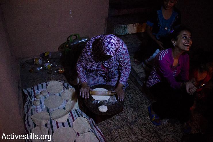 Alewa's wife prepares dough to bake bread for dinner. August 11, 2014. (Basel Yazouri/Activestills.org)