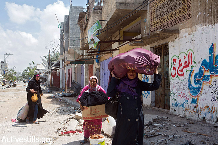 Palestinian women retrieve what belongings they can carry from their homes in Beit Hanoun, North Gaza, August 4, 2014. They had returned to their homes to quickly salvage what they could during a short ceasefire. Most Beit Hanoun residents had fled the heavily bombed areas and were staying in UNRWA schools or with relatives. (Anne Paq/Activestills.org)