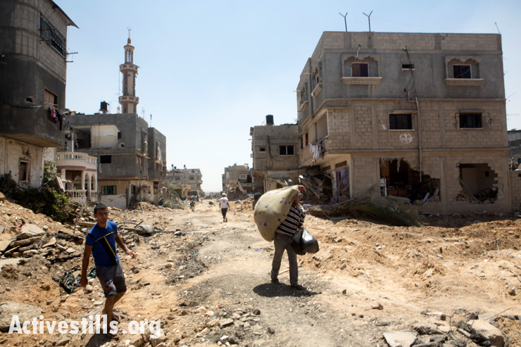 Palestinians salvage some of their belongings from the village of Khuza'a,  east of Khan Younis August 1, 2014.