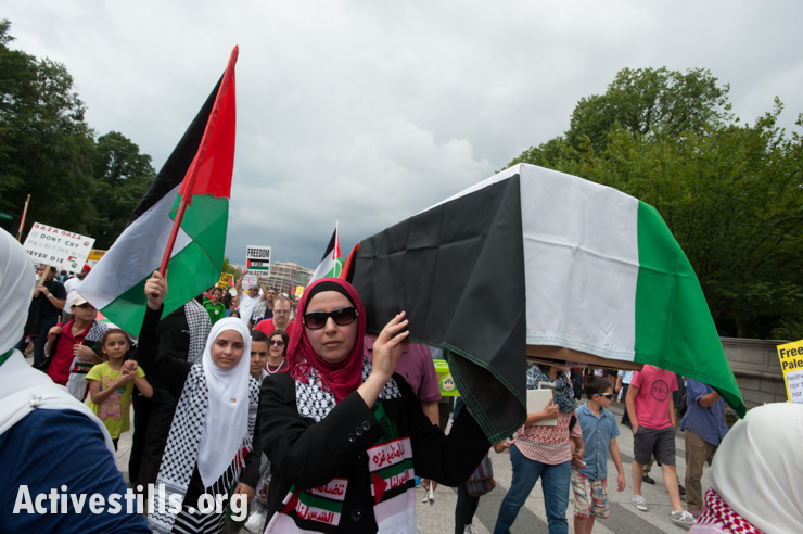 A protester carries a symbolic coffin to commemorate the victims of Israel's offensive on Gaza as thousands march in Washington, D.C., August 2, 2014. So far, Israeli attacks have killed at least 1,622 Palestinians, the majority of them civilians, including 326 children. (Activestills.org)