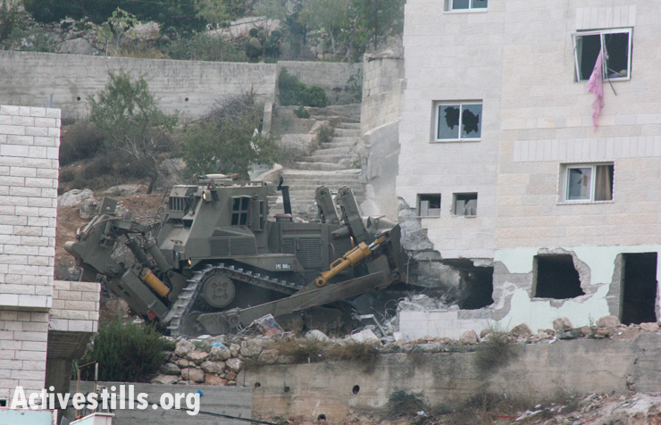 An Israeli military bulldozer destroys part of the family home of Zakaria Al-Aqra, age 24, after he was killed by an army raid in the West Bank village of Qabalan, August 11, 2014.(photo: Activestills.org)