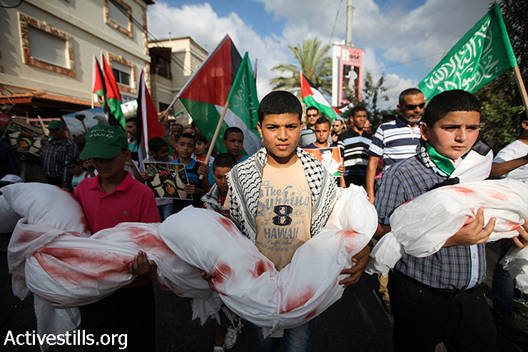 Palestinian youth living in Israel hold dolls wrapped in a white cloth, during a demonstration against the Israeli attack on Gaza and in support of the Palestinian people, in the northern village Tamra on August 2, 2014. (Faiz Abu-Rmeleh/Activestills.org)