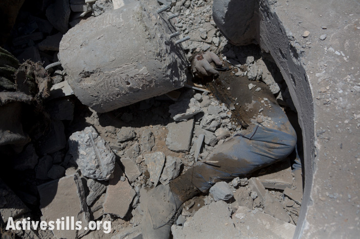 A body is seen under the rubble of a destroyed home in the village of Khuza'a, east of Khan Younis August 1, 2014.