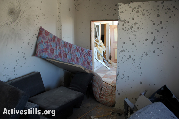 Damage from bullets and blast fragments cover the walls of the Al-Aqra family home, Qabalan, West Bank, August 11, 2014.(photo: Activestills.org)