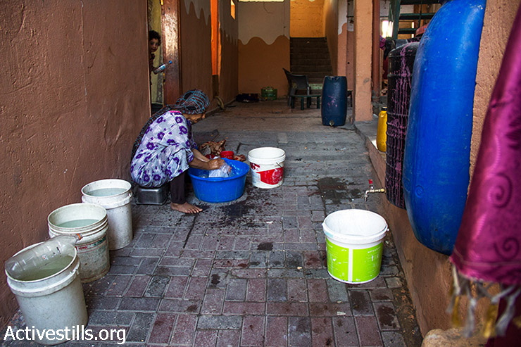 Since there is no electricity in the house, Abu Alaa's wife, Um Alaa, must hand washes clothes. August 12, 2014. (Basel Yazouri/Activestills.org)