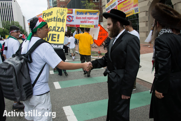A youth shakes hands with a member of the anti-Zionist orthodox Jewish group Neturei Karta as thousands march in Washington, D.C., to protest Israel's offensive in Gaza, August 2, 2014. So far, Israeli attacks have killed at least 1,622 Palestinians, the majority of them civilians, including 326 children. (Activestills.org)