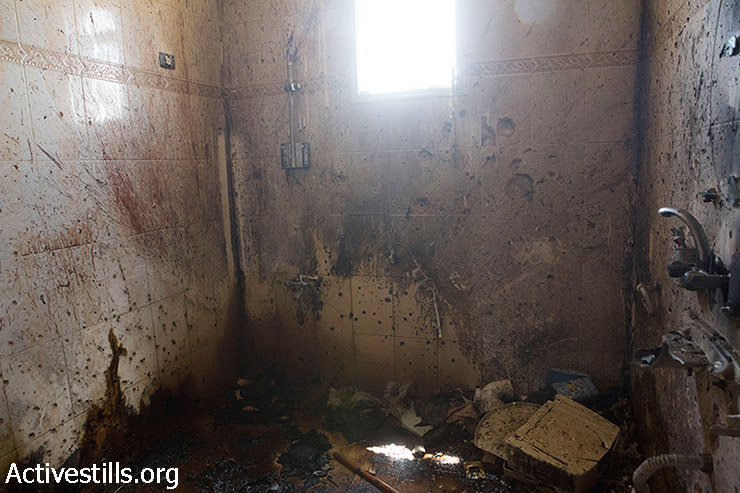 A bathroom where six bodies were found is covered with bullet holes, raising allegations of an execution by Israeli forces in Khuza'a, Gaza Strip, August 3, 2014. (Anne Paq/Activestills.org)