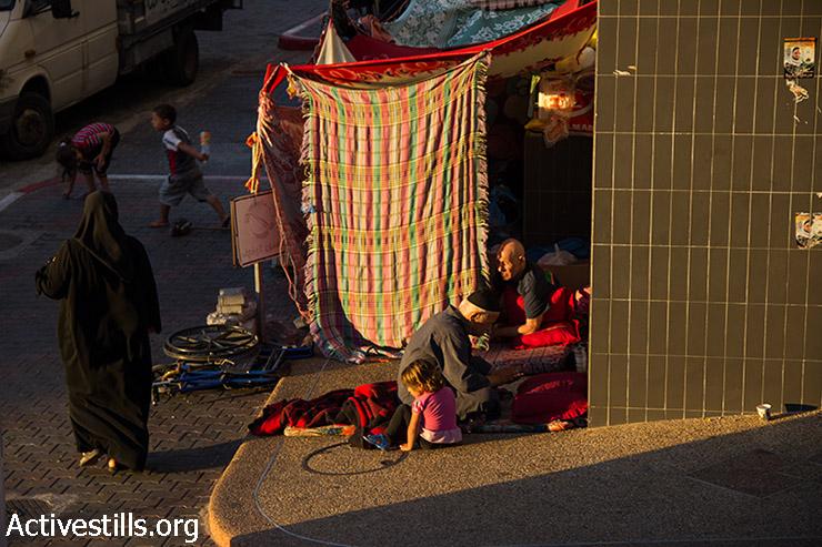 Gazans who evacuated their houses live in makeshift tents at Al-Shifa Hospital, August 9, 2014.  (Basel Yazouri/Activestills.org)