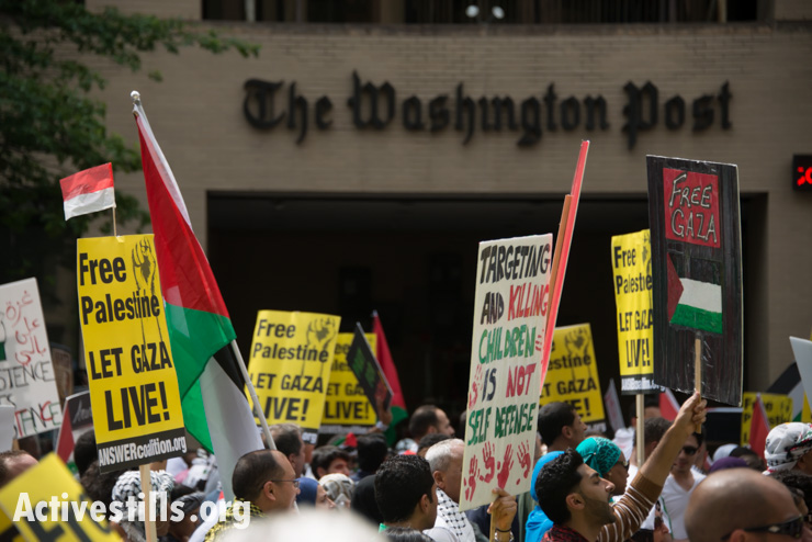 Marchers protesting Israel's offensive in Gaza pass the offices of The Washington Post newspaper in Washington, D.C., August 2, 2014. So far, Israeli attacks have killed at least 1,622 Palestinians, the majority of them civilians, including 326 children. (Activestills.org)