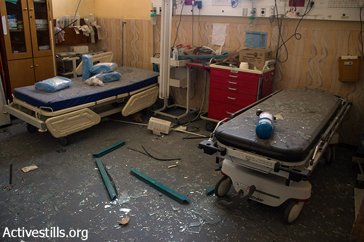 Shattered glass caused by Israeli attacks covers a room in Beit Hanoun Hospital, northern Gaza Strip, August 4, 2014. Most Beit Hanoun residents had fled the heavily bombed areas and have been staying in UNRWA schools or with relatives. (Basel Yazouri/Activestills.org)