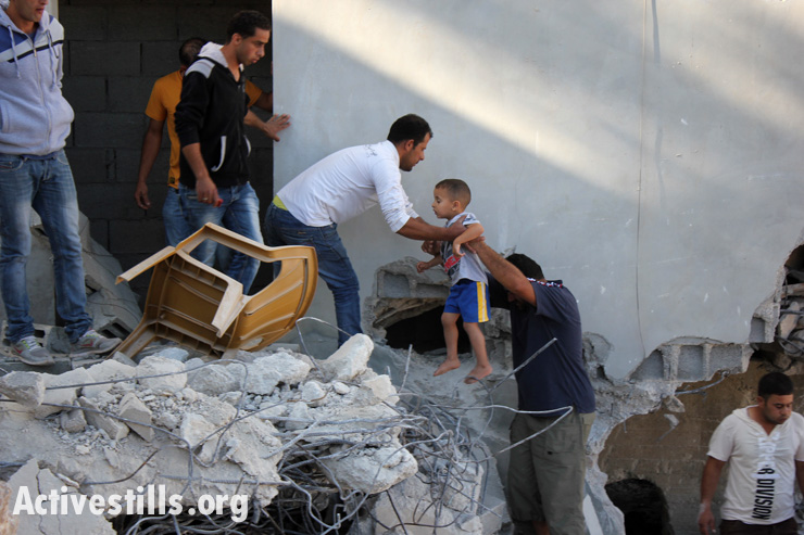 Members of the Al-Aqra family evacuate their house after it was severely damaged in a raid that killed Zakaria al-Aqra, age 24, Qabalan, West Bank, August 11, 2014. Zakaria was wanted by Israel. Six other people from the family were wounded during the operation which lasted for eight hours.(photo: Activestills.org)