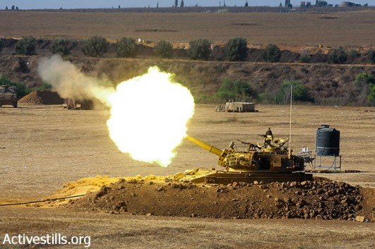 An Israeli artillery fires a shell towards the Gaza Strip from their position near Israel's border with the Gaza strip on July 24, 2014. (Yotam Ronen/Activestills.org)