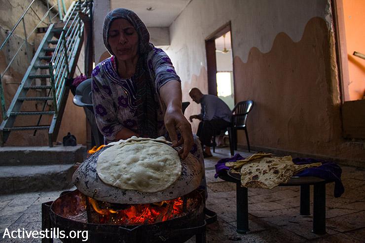 Um Alaa bakes breads for breakfast, August 12, 2014. (Basel Yazouri/Activestills.org)