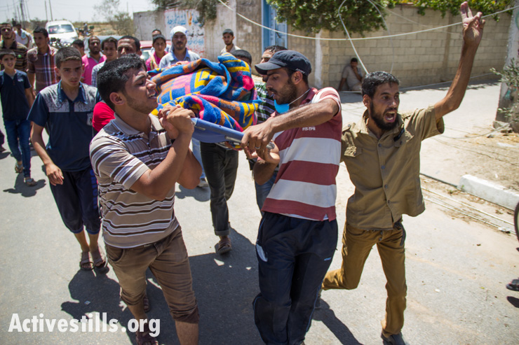 Palestinians remove bodies recovered from destroyed houses in Khuza'a village following bombardment by Israeli forces, Gaza Strip, August 1, 2014.