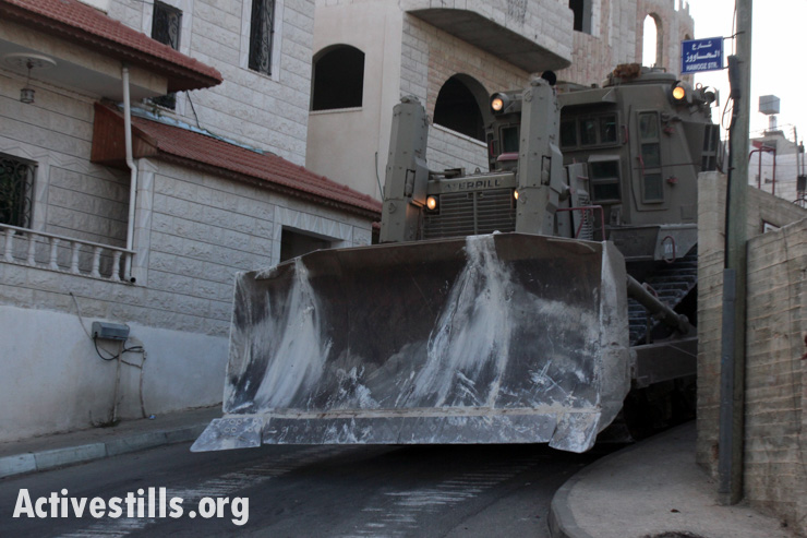 An Israeli bulldozer drives through the West Bank village of Qabalan, following a raid which killed Zakaria Al-Aqra and badly damaged his family home, August 11, 2014.(photo: Activestills.org)