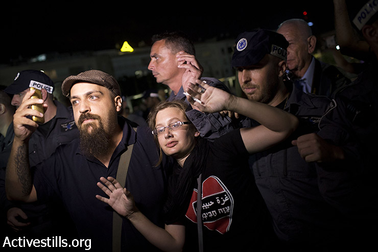 Israeli policemen push left-wing activists as they try to prevent them from staging a demonstration against the Israeli attack on Gaza, in central Tel Aviv, August 2, 2014. Police arrested 17 left-wing protesters as hundreds gathered outside Habima theater calling to end the attack on Gaza. (Oren Ziv/Activestills.org)