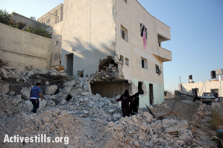 Palestinians assess the damage caused to the family house of Zakaria al-Aqra, age 24, who was killed by Israeli forces in the West Bank village of Qabalan, Nablus, August 11, 2014.(photo: Activestills.org)