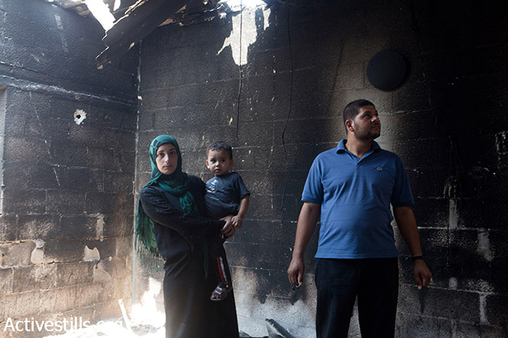 Members of the Al Kaferna family stand in their flat which was destroyed by Israeli strikes in Beit Hanoun, northern Gaza Strip, August 4, 2014. They went back to quickly salvage a few of their belongings during a short ceasefire. (Anne Paq/Activestills.org)