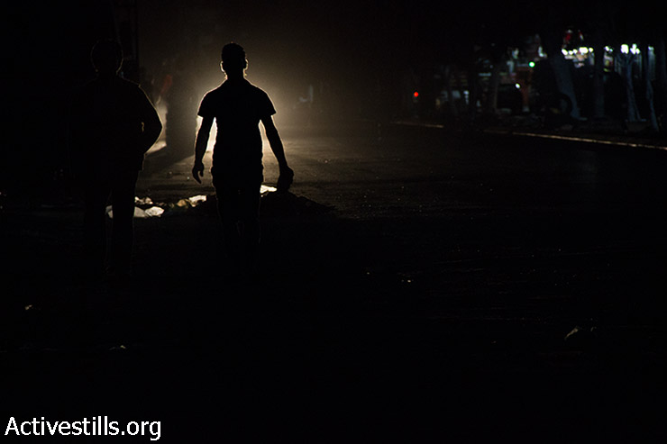 Gazans walk on streets in darkness after the Israeli bombing of the main electricity plant caused a continuous 7-day power cut throughout the Gaza Strip, August 9, 2014. (Basel Yazouri/Activestills.org)