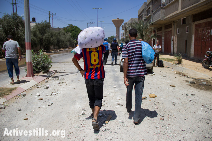 Palestinians recover what belongings they can from the Khuza'a neighborhood following bombardment by Israeli forces, Gaza Strip, August 1, 2014.