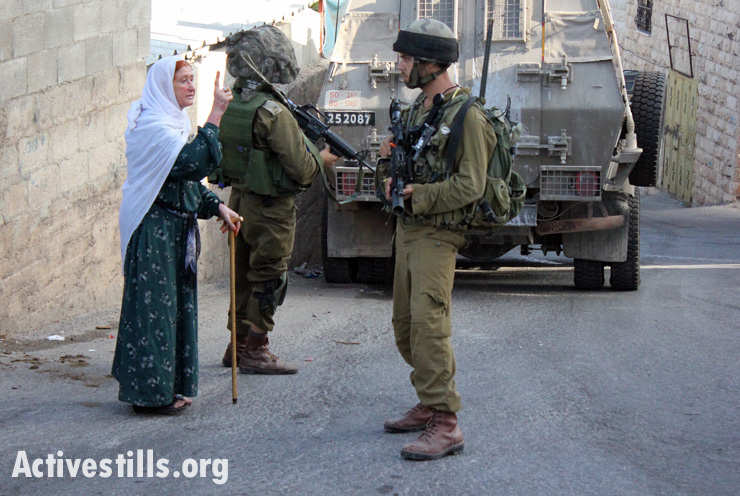A Palestinian woman shouts at Israeli soldiers during an army operation in which soldiers killed Zakaria al-Aqra, age 24, at his family house in the West Bank village of Qabalan, August 11, 2014. Qabalan village has been raided several times in the last two weeks by the Israeli army.(photo: Activestills.org)