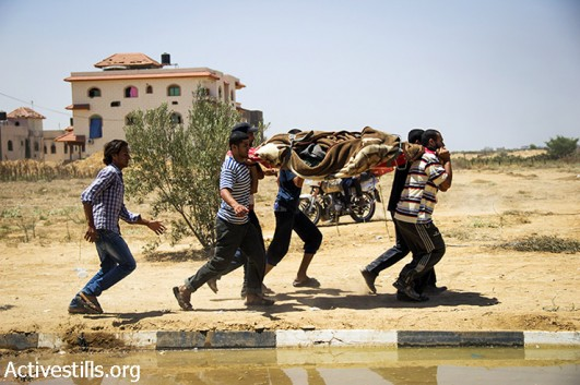 Palestinians carry a body recovered from destroyed houses in the village of Khuza'a, east of Khan Younis, Gaza Strip, August 1, 2014. Hundreds of residents returned to Khuza'a at the beginning of a ceasefire to recover bodies and salvage possessions. Khuza'a has been cut off from the rest of Gaza Strip and occupied by Israeli soldiers. It emined a closed military zone, and only International Committe of the Red Cross managed to secure a few brief incursions into the village to evacuate some of the injured, killed and the civilians. A large number of residents have been killed and injured, and many homes were destroyed. Most residents fled the Israeli attacks. (Anne Paq/Activestills.org)