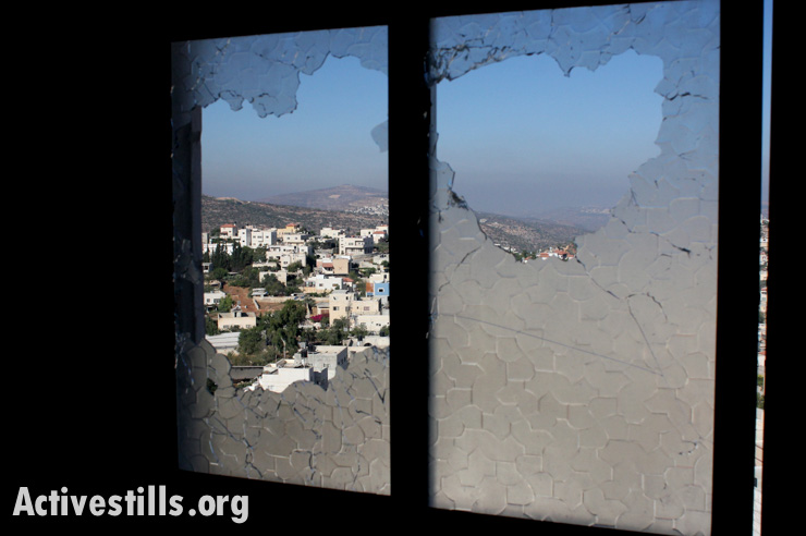 A view of the West Bank village of Qabalan through the broken windows of the Al-Aqra family house following an Israeli army raid that killed Zakaria Al-Aqra, age 24, August 11, 2014.(photo: Activestills.org)