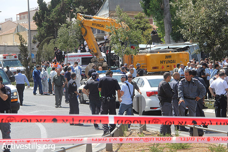 Policemen and medics gather after a Palestinian man went on a rampage in an industrial digger, running over a few people and flipping over a bus in Jerusalem, killing one man and injuring a few, August 4, 2014. (Faiz Abu-Rmeleh/Activestills.org)