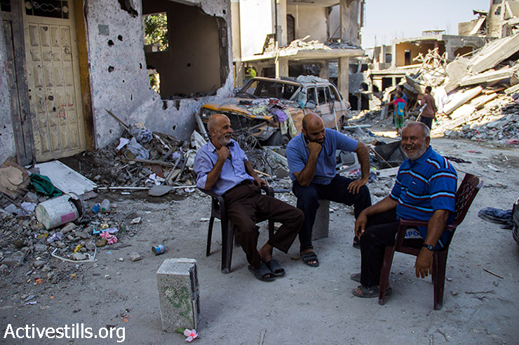 Abu Alaa sits with his neighbours exchanging jokes on the occupation army. August 12, 2014. (Basel Yazouri/Activestills.org)