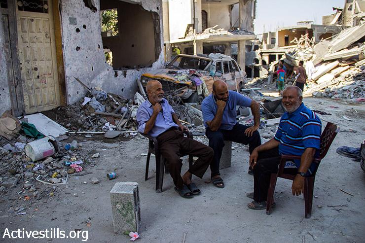Abu Alaa sits and exchanges jokes with is neighbors. August 12, 2014. (Basel Yazouri/Activestills.org)