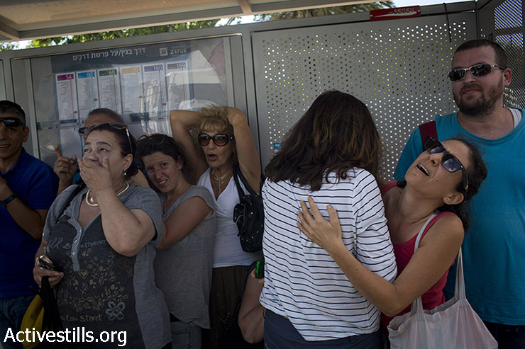 Israelis take cover near a bus stop in a street in central Tel Aviv during a siren alarm as a rocket is launched from Gaza strip, August 3, 2014. (Oren Ziv/Activestills.org)