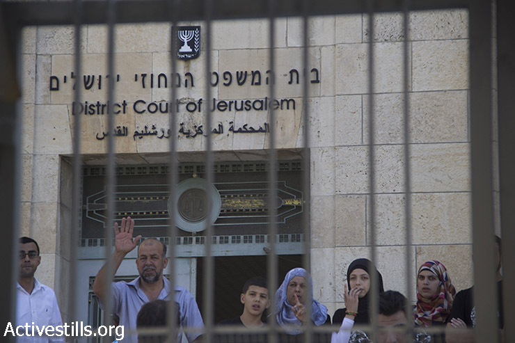 The family of 16-year old Mohammed Abu Khdeir, who was kidnapped from east Jerusalem on July 2 and burned to death in a suspected revenge attack for the abduction and killing of three Israeli teenagers, stand outside the District Court in Jerusalem, after a court hearing for three of the Israeli suspects on August 6, 2014. (Faiz Abu-Rmeleh/Activestills.org)