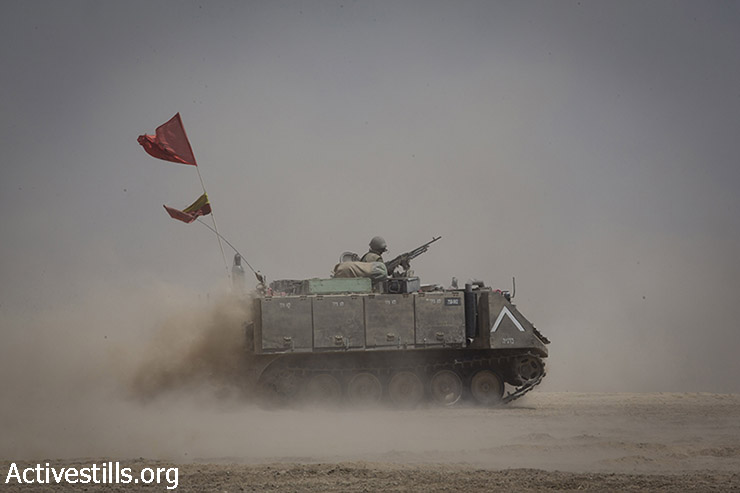 An Israeli soldier is seen on board an APC near the border between Israel and the Gaza Strip while returning from the Strip, August 5, 2014, after Israel announced that all of its troops had withdrawn from Gaza. (Oren Ziv/Activestills.org)