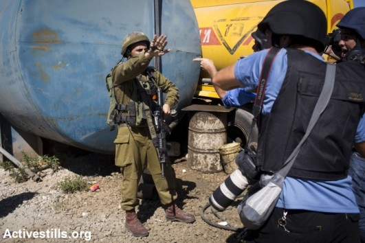 An Israeli soldiers arguing with media staff after soldiers shot a journalist with a live bullet during clashes of Palestinian supporters of Hamas with Israeli army forces, following a protest against the Israeli attack on Gaza at the DCO checkpoint near Ramallah, West Bank, July 25, 2014 (photo: Activestills)