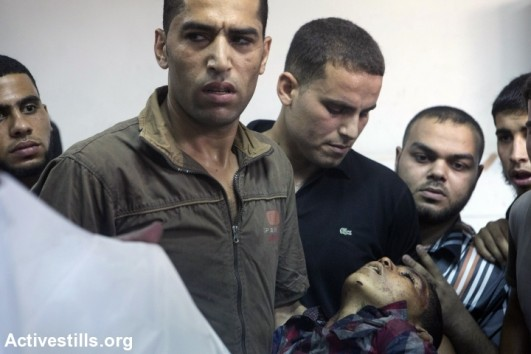 A relative carries one of the children killed earlier in an attack in a playground in al-Shati refugee camp, Gaza City, July 28, 2014. Reports indicate that 10 people, mostly children, were killed and 40 injured during the attack which took place on the first day Eid (photo: Activestills)