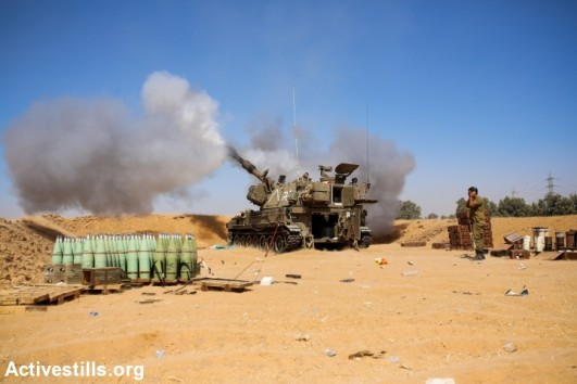An Israeli artillery fires a shell towards the Gaza Strip from a position near Israel's border with the Gaza Strip on Augost 1, 2014 after the proposed three-day truce that began at 0500 GMT collapsed amid a deadly new wave of bloodshed and the apparent capture of an Israeli soldier by Hamas (photo: Activestills)