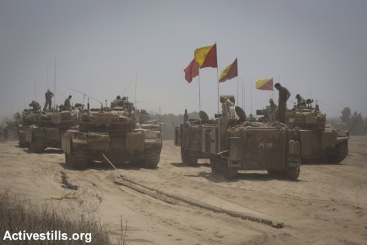 An Israeli soldier sit on top of Merkava tanks near the border between Israel and the Gaza Strip while returning from the Gaza strip, August 5, 2014, after Israel announced that all of its troops had withdrawn from Gaza (photo: Activestills)