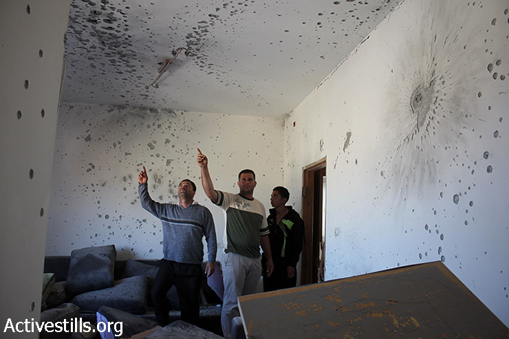 Palestinians check the damage caused to the house of wanted Palestinian Zakaria al-Aqra, 24, who was killed by Israeli forces in the West Bank village of Qabalan, Nablus, August 11, 2014. Six people from his family were wounded and parts of his house were destroyed during the 8-hour operation. Qabalan village has been raided several times in the last two weeks by the Israeli army. (Ahmad Al-Bazz/Activestills.org)