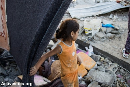 A Palestinians child stands in front of a destroyed house in Beit Hanoun following bombardment by Israeli forces, northern Gaza Strip, August 11, 2014. According to OCHA, 16,800 homes in the Gaza Strip have been destroyed or severely damaged leaving 370,000 displaced. (photo: Activestills)