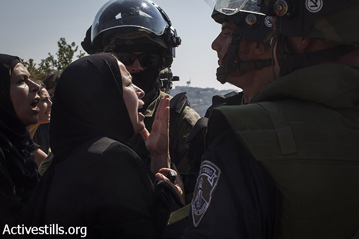 Palestinian women argue with Israeli soldiers after a Palestinian youth was shot with live ammunition and was taken by the army during the weekly protest against the occupation in the West Bank village of Nabi Saleh, August 15, 2014. (Keren Manor/Activestills.org)