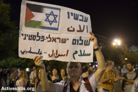 Israelis take part in a protest calling for peace negotiations between Israel and Palestinian, Tel Aviv, on August 16, 2014. Thousands of demonstrators gathered on Saturday for a pro-peace rally under the slogan: 'Changing Direction: Toward Peace, Away From War.' (photo: Activestills)