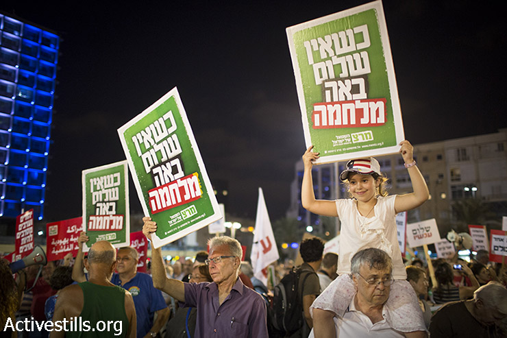 """Israelis hold signs reading, """"When there is no peace, war comes"""" during a demonstration calling for negotiations between Israel and the Palestine on August 16, 2014 in Tel Aviv, Israel. Thousands of demonstrators gathered Saturday evening for a pro-peace rally under the slogan, """"Changing Direction: Toward Peace, Away From War."""" (Oren Ziv/Activestills.org)"""