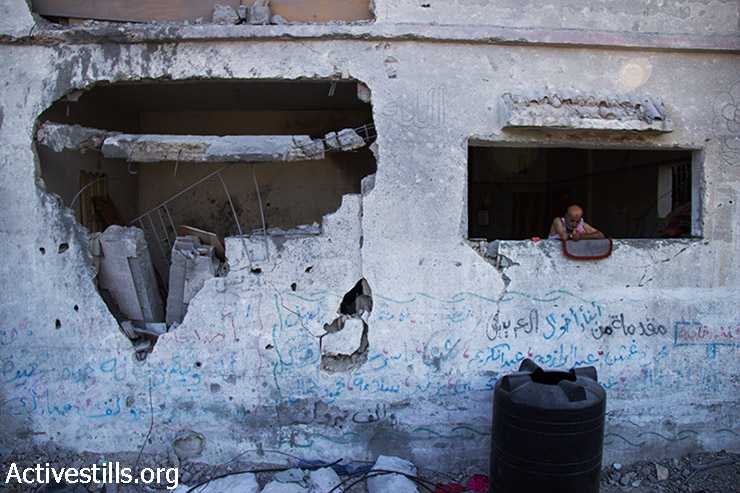 Ibrahim Abu Odeh (Abu Alaa), 60 years old, stands at his window in the early morning, examining what's left of his neighborhood. Next to him is one of the rooms of his house, completely destroyed. Beit Hanoun, Gaza Strip, August 12, 2014. Abu Alaa lives in a three-story building that has six apartments, occupied by his five married sons and their families, 33 people in total, 21 of them children. He was forced to flee his house with his family, along with the residents of Beit Hanoun due to the Israeli attack. They took shelter in the Jabalya Secondary School for Boys, in Jabalya Refugee Camp, but returned to their bombed home because of harsh condition in the school. Since then they have been living in their destroyed house without electricity or gas. (Basel Yazouri/Activestills.org)