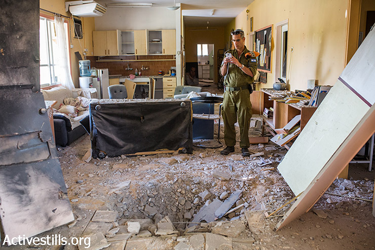 An Israeli soldier photographs the scene in which a mortar shot from the Gaza Strip directly hit a house, southern Israel, August 21, 2014. (Yotam Ronen/Activestills.org)