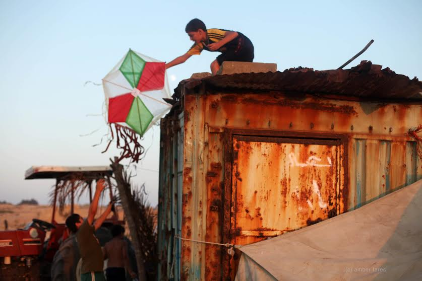 Musa fetching his kite from a roof while flying it on the beach in Gaza, during the filming of Flying  Paper in July 2010. (photo: Amber Fares)